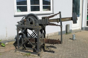 På fortovet ved Rostrup Autoværksted står en gammel, mekanisk hammer